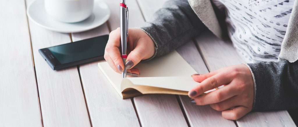 Woman writing into a notebook